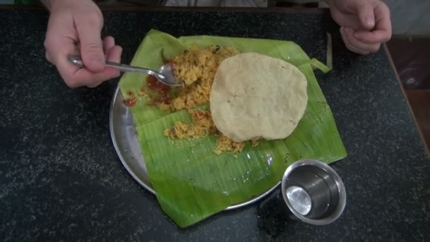 Tourist eating vegetarian rice  on banana leaf in south India restaurant