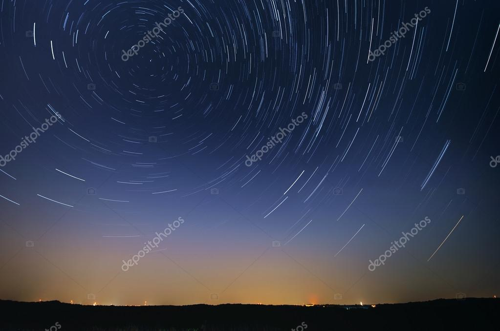 Startrail landscape of moving stars in night sky over the city