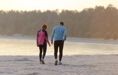 Young man and woman walking along the waterfront