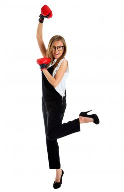 Winning business woman celebrating wearing boxing gloves and bus