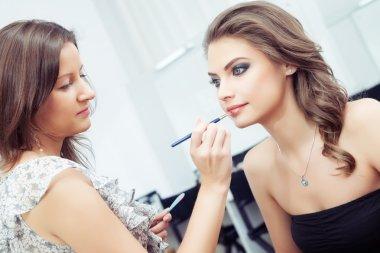 Make-up artist applying lipstick