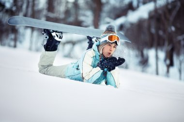 Female snowboarder blowing snow