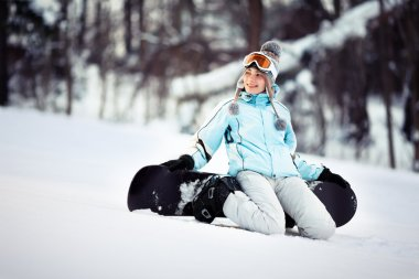 Young female snowboarder sitting