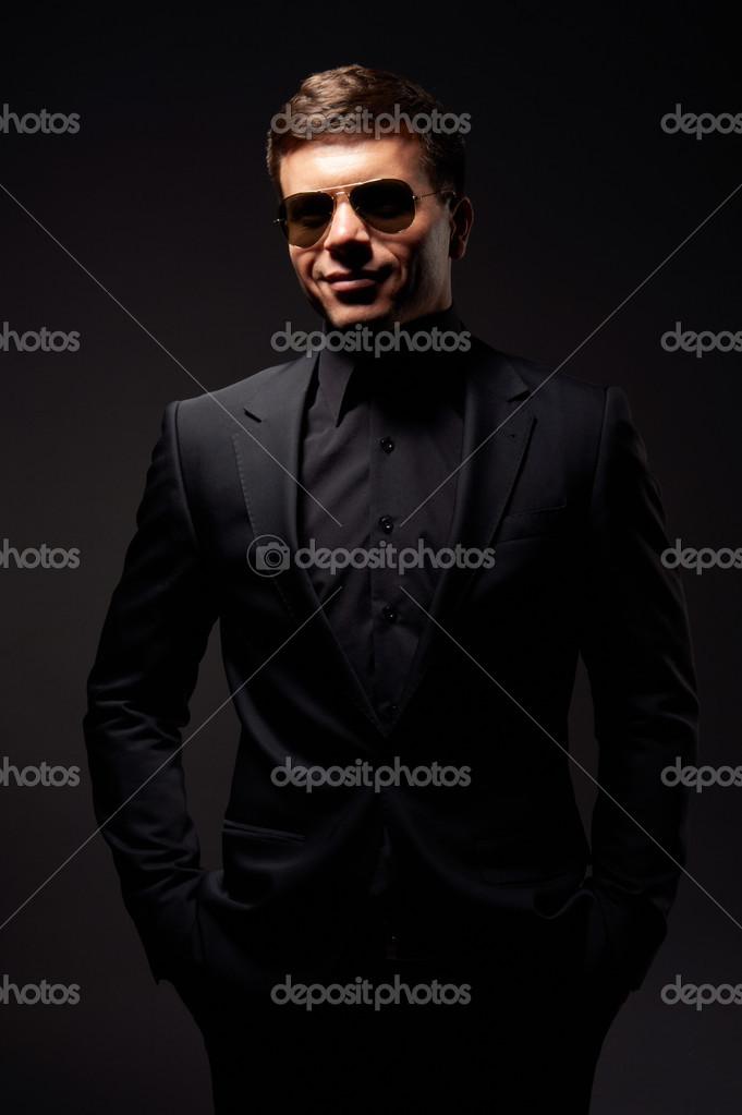 hombre sonriente elegante ropa formal negro y gafas de sol studio dispar sobre el fondo oscuro u foto de