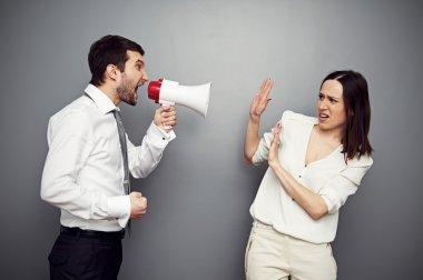 boss screaming in megaphone at the woman