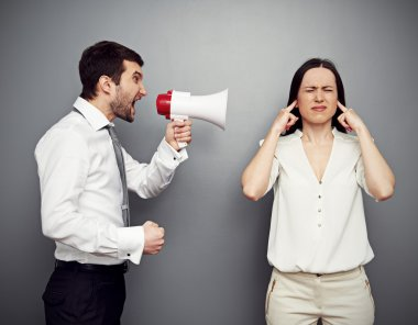 man screaming in megaphone at the woman