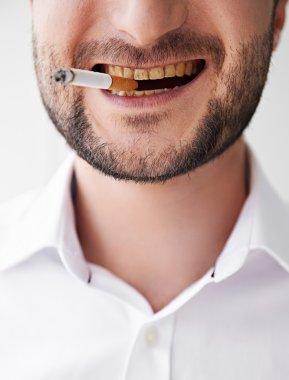 smoking man with dirty yellow teeth