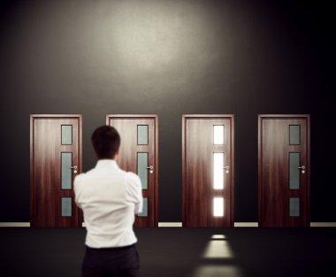 man looking at four doors