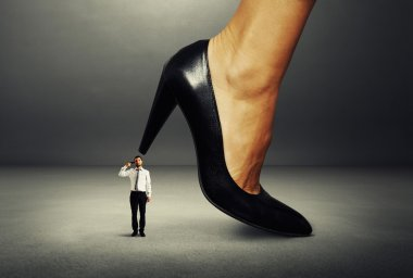 man with gun under big female heel