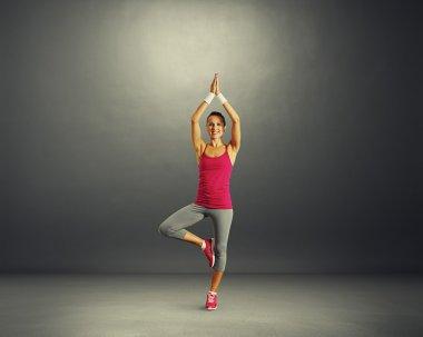 Smiley young woman practicing yoga in dark studio stock vector