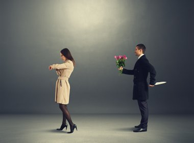 man with flowers behind woman