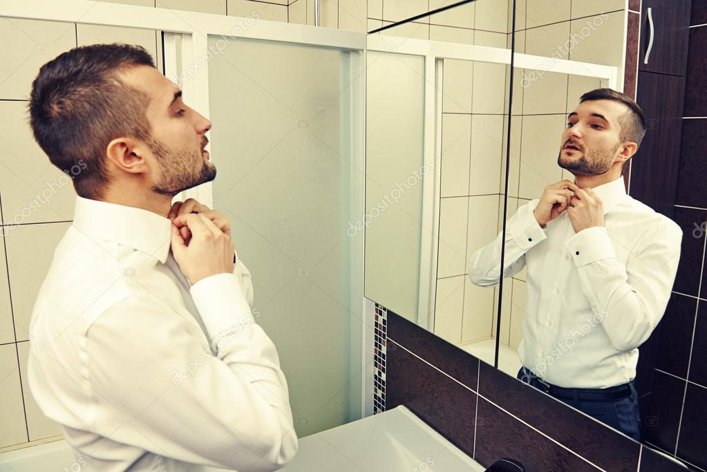 Handsome man looking at mirror and get dressed