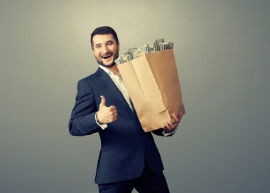 man holding paper bag with money