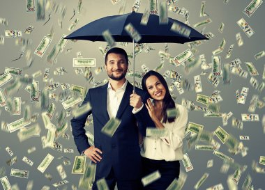 Smiley successful couple with umbrella standing under money rain stock vector