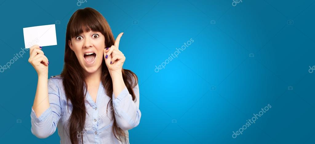 Portrait Of A Girl Holding And Pointing Up On Blue Background