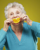 Fotografie Portrait of senior woman holding a orange slice in front of her