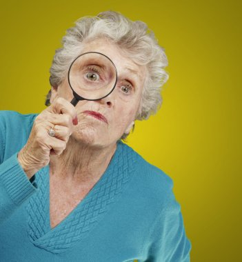 Portrait of senior woman looking through a magnifying glass over