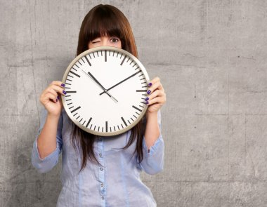 Woman Holding Clock Winking