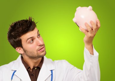 Young Doctor Holding A Piggy Bank