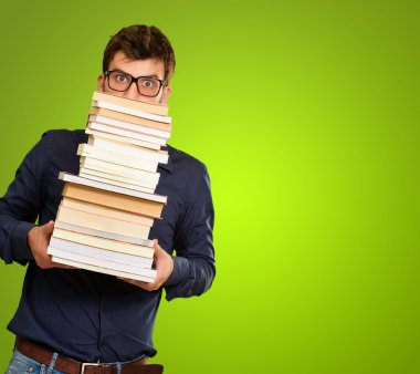 Young Man Holding Stack Of Books