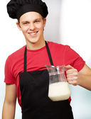 portrét mladého kuchaře muž, který držel sklenici mléka vnitřní