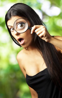 Young woman surprised looking through a magnifying glass against
