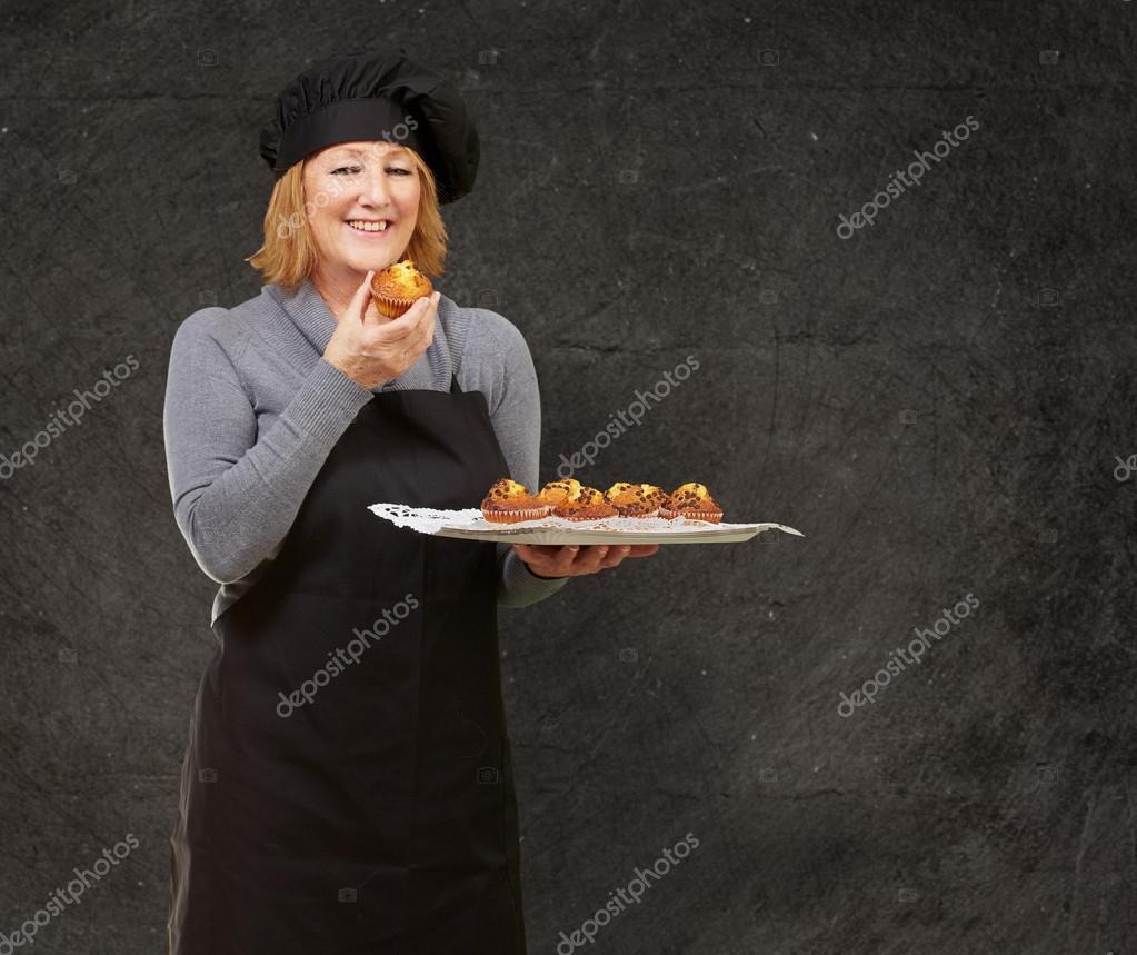 Porträt des mittleren Alter Koch Frau hält eine hausgemachte Muffin ...