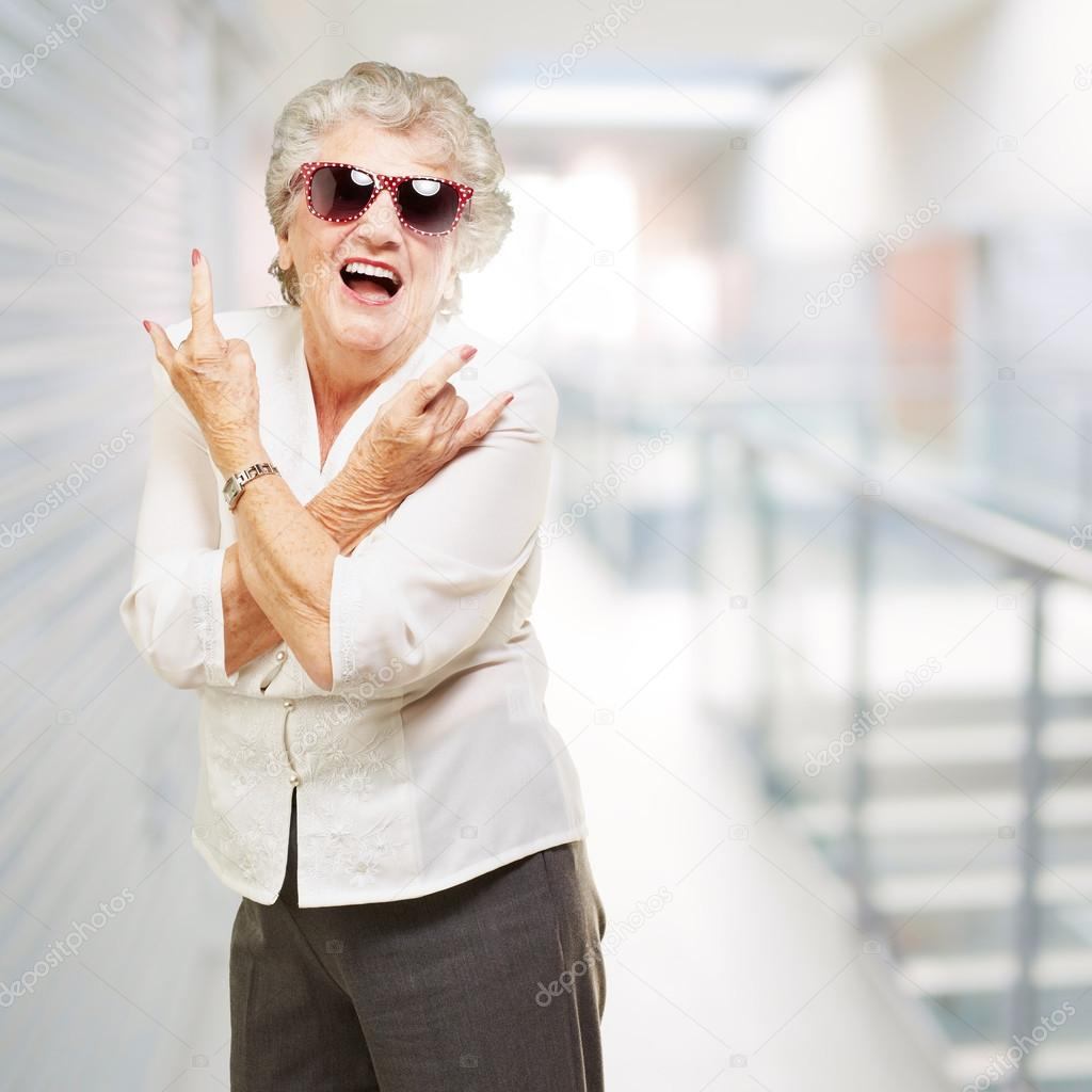 Portrait of senior woman smiling and wearing sunglasses at moder