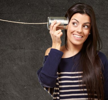 Young woman hearing using a metal tin can against a grunge wall