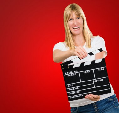 Happy Woman Holding Clapper Board against a red background stock vector