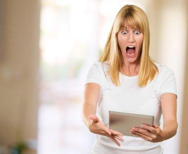 Shocked Woman Looking At Digital Tablet