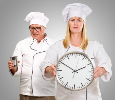 Female Chef Holding Clock In Front Of Male Chef