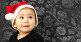 Photo Baby boy wearing a christmas hat and looking up
