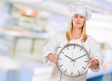 Female Chef Holding Clock