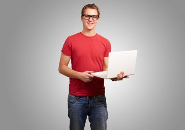 portrait of young student man holding laptop over grey backgroun