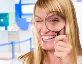 šťastný lékař při pohledu přes zvětšovací sklo