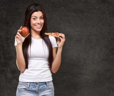 Female Holding A Piece Of Pizza And A Apple