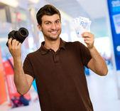 junger Mann mit Kamera und Euro Währung