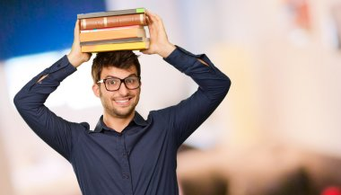 Young Happy Man With Books On Head