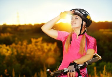 Cycling girl looking to the sunset