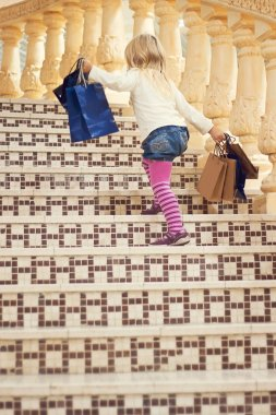 girl 3 years old goes up the stairs with shopping