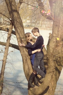 Young beautiful couple hugging against the tree