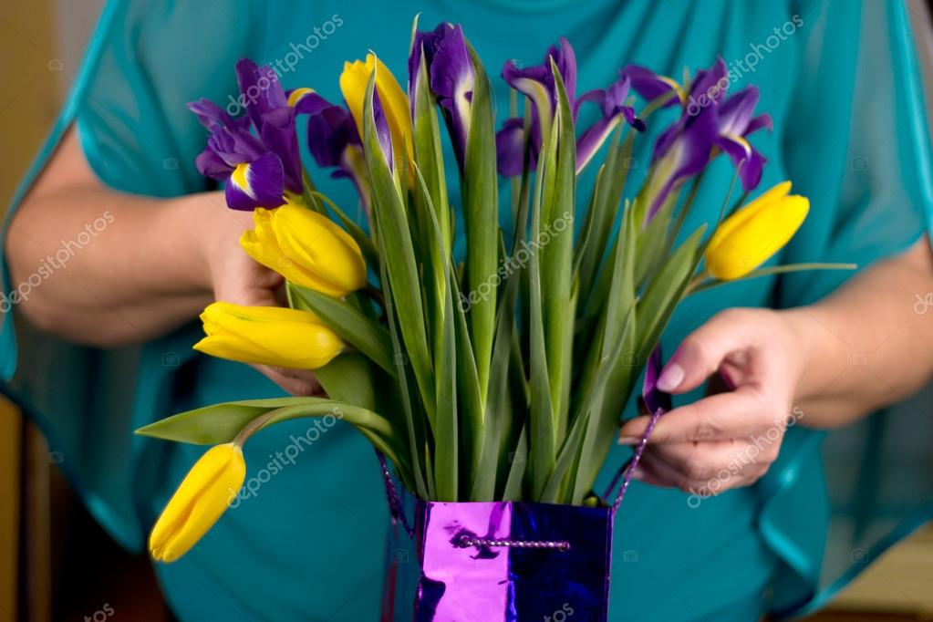 Woman holding a yellow tulips and blue irises