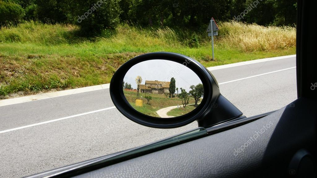Farmhouse reflected in a rear-view mirror of a car