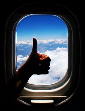 Photo of person arm with thumb up in the plane, blue sky with white clouds through airplane window frame, happy traveller, silhouette of tourist hand with gesture ha stock vector