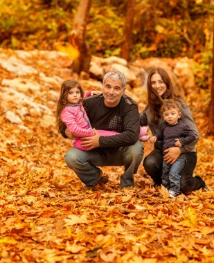 Happy family in autumnal forest