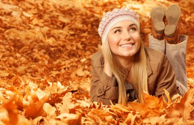 Girl lying down on autumnal leaves