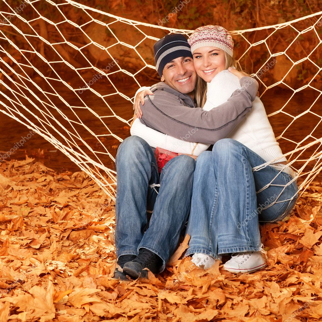 Young family hugging in hammock