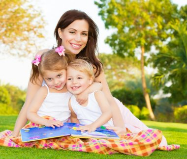 Picture of young happy family, beautiful mother with two cute kids having fun outdoors in spring, pretty female with son and daughter sitting down on green meadow on backyard, daycare concept stock vector