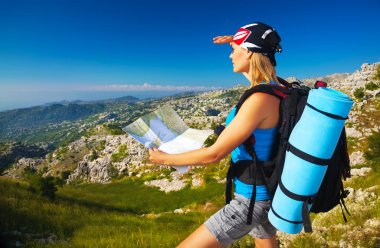 Active girl with map in the mountains